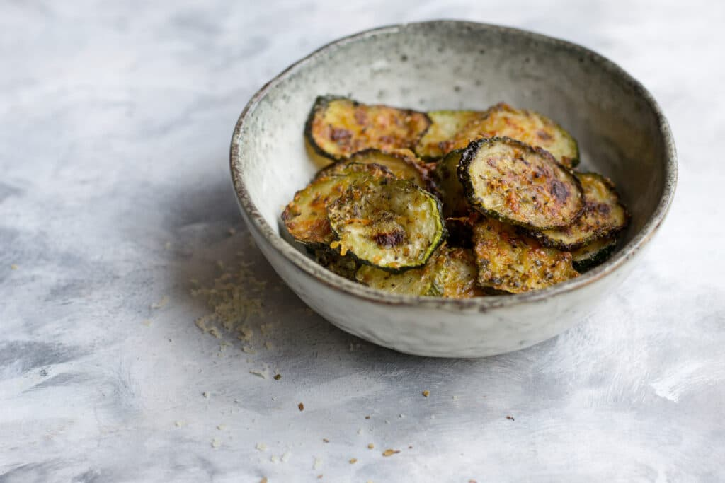 Baked keto courgette chips in a small bowl