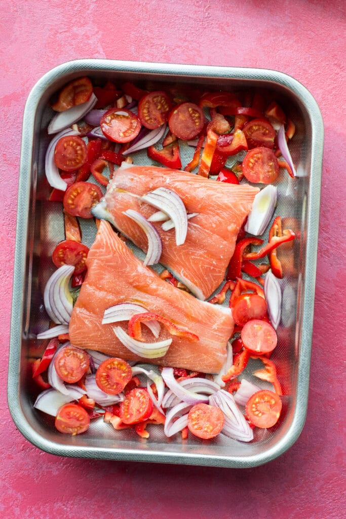 Raw salmon and vegetables in a baking tray