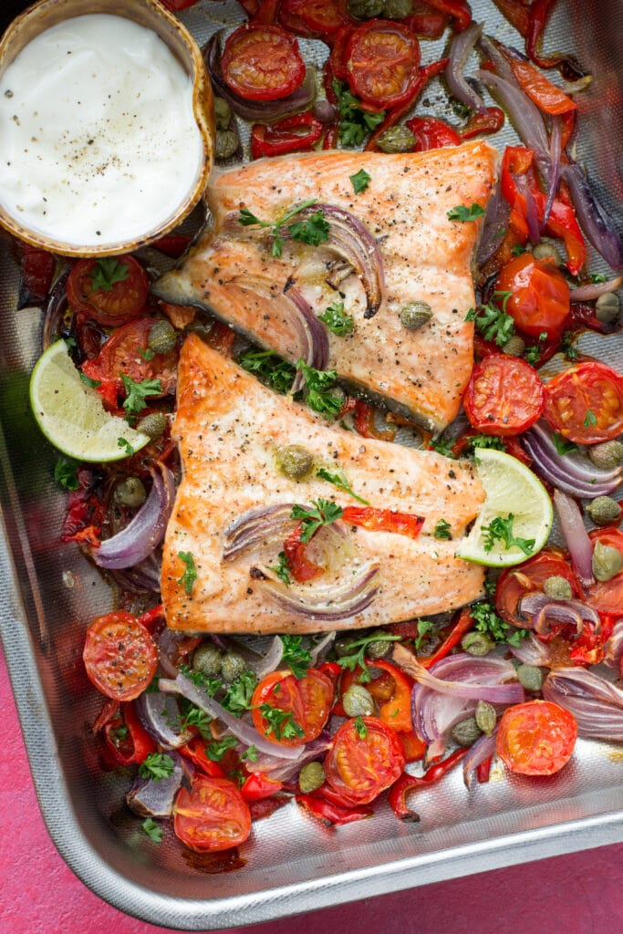 Cooked salmon and vegetables in a baking tray with cream cheese