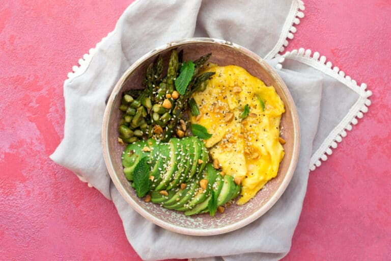 Eggs, avocado and asparagus in a bowl with mint and nut granola