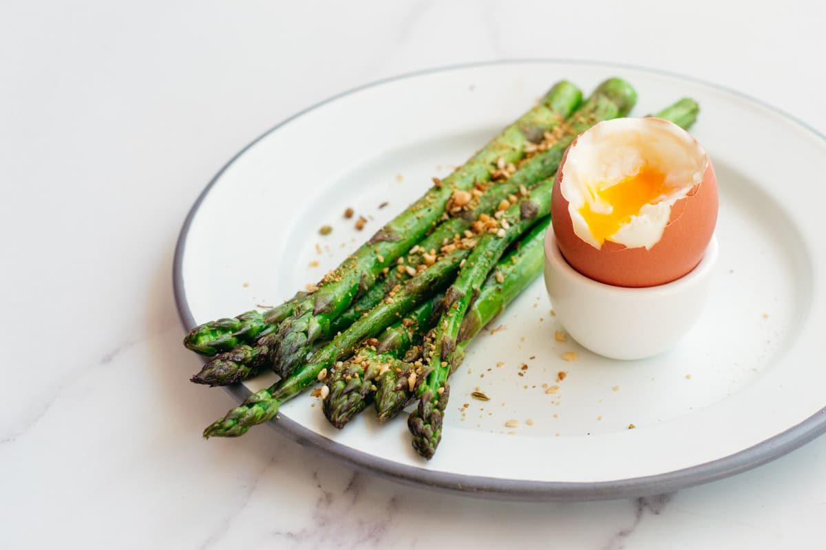 Cooked asparagus and a soft boiled egg