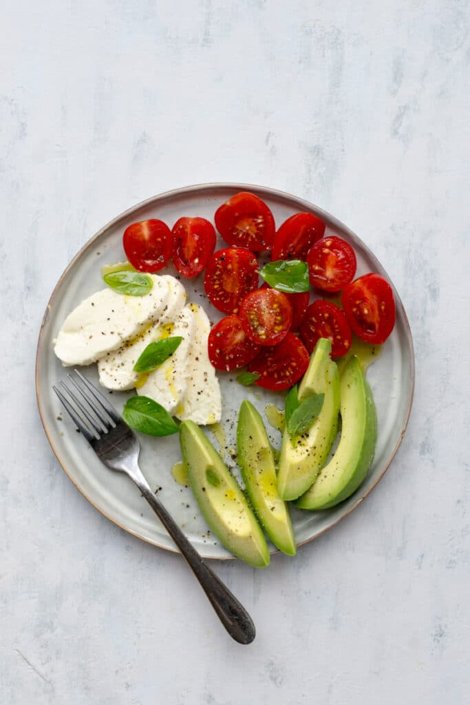 Caprese salad with avocado on a plate