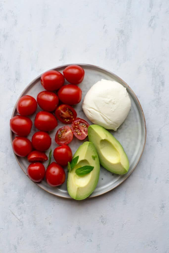 Ingredients for Caprese salad with avocado on a plate